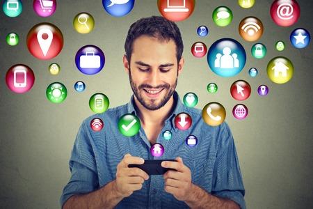 medios de informaci�n: tecnolog�a de comunicaci�n m�vil concepto de alta tecnolog�a. Hombre feliz que usa mensajes de texto en los iconos de aplicaciones de medios sociales de tel�fonos inteligentes que vuelan de tel�fono celular aislado fondo de la pared gris. Plan de datos 4G