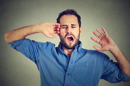 perezoso: Hombre soñoliento joven bostezo que estira los brazos hacia atrás aislado sobre fondo gris de la pared. La privación del sueño, el agotamiento, el concepto de la pereza