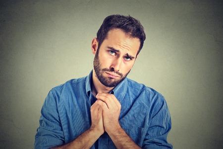 preguntando: Primer retrato de hombre joven desesperada que muestra las manos entrelazadas, bastante contento con el azúcar en la parte superior aislada sobre fondo gris de la pared. La emoción humana sentimientos de expresión facial, el lenguaje corporal