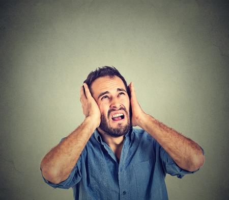 Ritratto giovane infastidito, infelice, stressato uomo che coprono le orecchie, guardando in alto, per dire, smettere di fare rumore forte, dandomi il mal di testa isolato su sfondo grigio con spazio di copia. Reazione emozione negativa Archivio Fotografico - 46736926