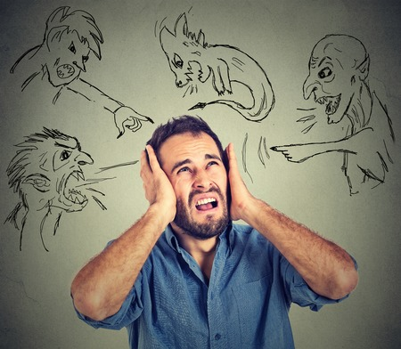 Stressed young man covers his ears with his hands evil guys pointing fingers at him blaming Stockfoto