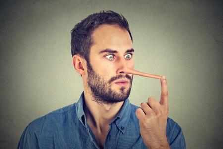 긴 코를 가진 남자 회색 벽 배경에 고립입니다. 거짓말 쟁이 개념입니다. 인간의 얼굴 표정, 감정, 감정.