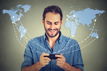 business  deal: Modern communication technology mobile phone high tech, web connection concept. Happy business man holding smartphone connected browsing internet worldwide world map background. 4g data plan provider