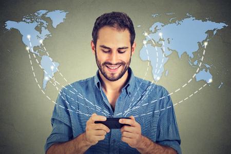 koncepció: Modern kommunikációs technológia mobiltelefon high-tech, webes kapcsolat fogalmát. Boldog üzletember, aki okostelefon csatlakozik böngészés internet világméretű világtérképen háttérben. 4g adat terv szolgáltató