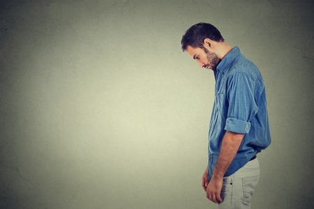 Side profile sad lonely young man looking down has no energy motivation in life depressed isolated on gray wall background