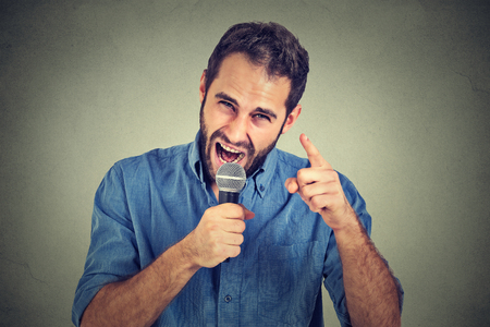 propaganda: Angry man screaming in microphone isolated on grey wall background. Negative face expressions, emotions, feelings. Propaganda, breaking news, power, social media concept