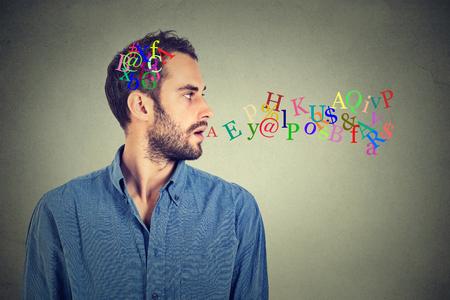 volar: Side hombre retrato de vista hablando con letras del alfabeto en la cabeza y que sale de la boca abierta aislada en el fondo gris de la pared. Expresiones faciales humanas, emociones. Comunicaci�n, el concepto de inteligencia Foto de archivo