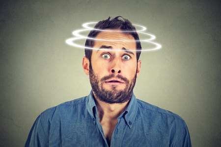 disbelief: Head is spinning. Surprise astonished man. Closeup portrait man looking surprised in full disbelief wide open mouth isolated grey wall background. Human emotion face expression body language. Stock Photo