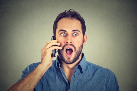 in shock: Shocked man talking on mobile phone