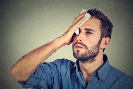 fiebre: Hombre cansado subrayó sudar la fiebre con dolor de cabeza aislado en el fondo gris de la pared. Preocupado hombre limpia el sudor de su rostro