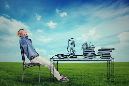 Young business man relaxing at his desk outdoors in the middle of a green meadow, daydreaming