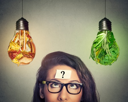 wellness: Woman in glasses question mark on head thinking looking up at junk food and green vegetables shaped as light bulb isolated on gray background. Diet choice right nutrition healthy lifestyle concept