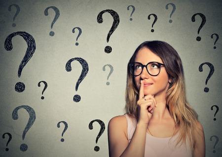 personen: Denken zakelijke vrouw met een bril kijken op vele vragen teken geïsoleerd op een grijze muur achtergrond