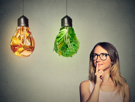 the right choice: Portrait beautiful woman in glasses thinking looking up at junk food and green vegetables shaped as light bulb isolated on gray background. Diet choice right nutrition healthy lifestyle concept