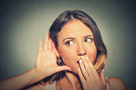 hearsay: Closeup portrait surprised young nosy woman hand to ear gesture carefully intently secretly listening juicy gossip conversation news isolated grey background. Human face expression. Privacy violation Stock Photo