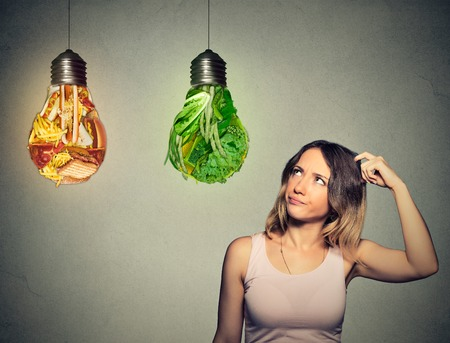 thin bulb: Portrait beautiful woman thinking looking up at junk food and green vegetables shaped as light bulb isolated on gray background. Diet choice right nutrition healthy lifestyle concept