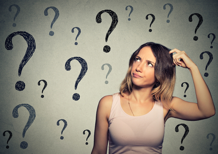 Thinking young woman with looking up at many questions mark isolated on gray wall background
