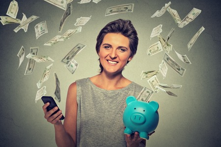 scholarship: Technology online banking money transfer, e-commerce concept. Happy young woman with smartphone piggy bank dollar bills banknotes flying away from screen isolated on gray wall office background. Stock Photo
