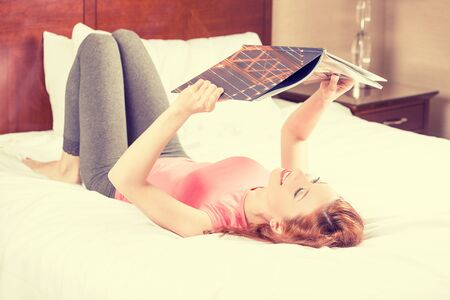 travel guide: Smiling young woman lying in bed while reading a magazine, travel guide Stock Photo