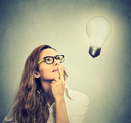Closeup beautiful girl thinks looking up at bright light bulb isolated on gray wall background. Idea, business, education and people concept. Face expression