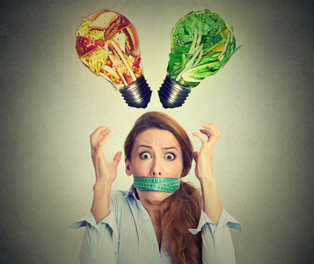 Diet restriction stress concept. Young frustrated woman with a measuring tape around her mouth junk food and green vegetables shaped as light bulb above head. Face expression. Right nutrition choice Stock Photo