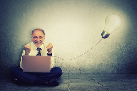 plugged in': Senior man working on computer with light bulb plugged in it celebrates business success