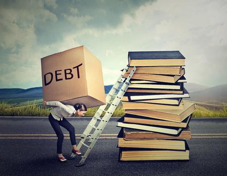 educaci�n: Concepto de la deuda de pr�stamos estudiantiles. Mujer joven con la pesada caja total de la deuda llevarla hasta la escalera educaci�n Foto de archivo