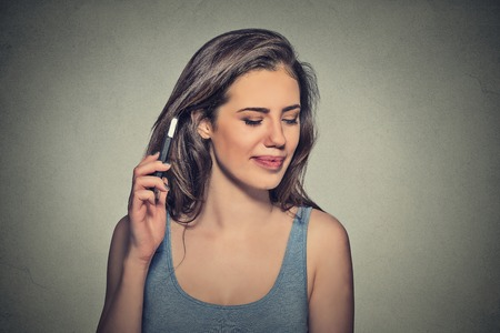 ear phones: young woman displeased on phone with headache. Upset unhappy girl talking on phone isolated gray background. Negative human emotion face expression feeling life reaction. Cellular radiation concept