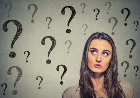 Portrait thinking young business woman looking up at many question marks isolated on gray wall background