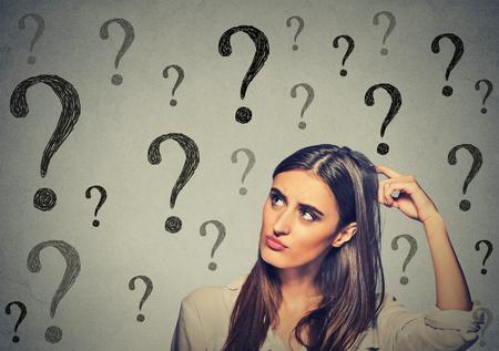 Portrait verwirrt denken junge Frau verwirrt den Kopf kratzen sucht nach einer Lösung suchen auf viele Fragezeichen isoliert auf grauen Wand Hintergrund. Menschliches Gesicht Ausdruck