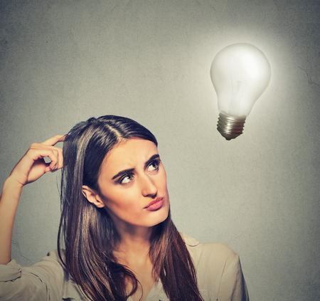 fun at work: Closeup portrait beautiful girl woman thinks looking up at bright light bulb isolated on gray wall background. Idea, business, education and people concept. Human face expression