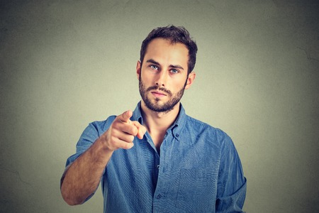 Portrait of a angry young man pointing finger at you camera gesture isolated on gray wall background Stockfoto