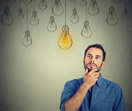 negócio: Retrato pensamento do homem considerável que olha-se com o bulbo idéia luz acima da cabeça isolado no fundo cinzento da parede