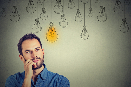 above head: Portrait thinking handsome man looking up with idea light bulb above head isolated on gray wall background