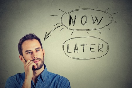 later: Now or later. Man thinking looking up isolated on grey wall background. Human face expression