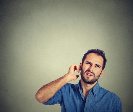 beau jeune homme: Gros plan portrait homme se gratter la t�te, � r�fl�chir profond�ment sur quelque chose, levant les yeux, isol� sur fond gris mur. Facial expression, �motion, sentiment, le langage du corps de signe humain Banque d'images