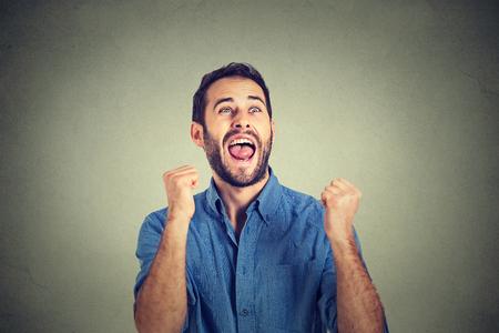 Erfolg: Detailansicht Portrait glücklich erfolgreicher Student, isoliert Geschäftsmann zu gewinnen, gepumpt Fäusten Erfolg feiert grauen Wand Hintergrund. Positive menschlichen Emotionen Gesichtsausdruck. Leben Wahrnehmung, Leistung