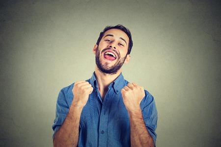 puños cerrados: Retrato del primer estudiante exitoso, aislado hombre de negocios de éxito ganadora, puños bombeados celebrando fondo de la pared gris feliz. Expresión facial emoción humana positiva. Percepción vida, logro
