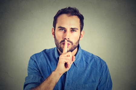 quiet: young handsome man giving Shhhh quiet, silence, secret gesture isolated on gray wall background Stock Photo
