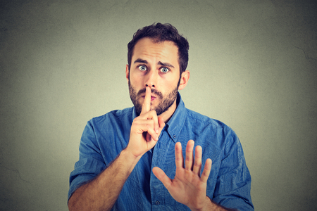 jonge knappe man geven Shhhh rust, stilte, geheim gebaar op een grijze muur achtergrond Stockfoto
