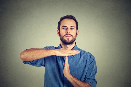 out time: Young man giving showing time out hands gesture isolated on gray wall background Stock Photo