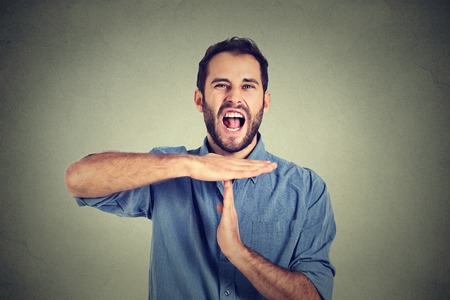 stop: Young man showing time out hand gesture, frustrated screaming to stop isolated on grey wall background. Too many things to do overwhelmed. Human emotions face expression reaction