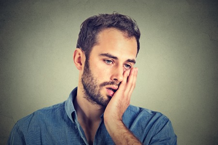 desperate: retrato de hombre infeliz desesperada aislada sobre fondo gris de la pared