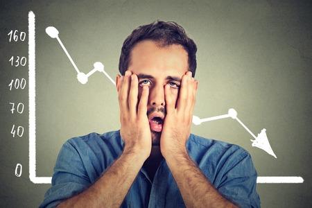 Portrait frustré souligné jeune homme désespéré avec la charte graphique du marché financier de descendre sur le gris mur de bureau fond. Économie pauvre concept de crise financière. L'expression du visage, l'émotion