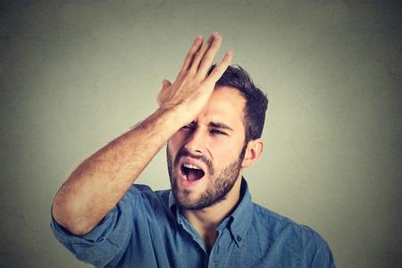 Betreurt verkeerd doen. Close-up portret dwaze jonge man, sloeg de hand op het hoofd met een duh ogenblik geïsoleerd op grijze achtergrond. Negatieve menselijke emotie gelaatsuitdrukking gevoel, lichaamstaal, reactie