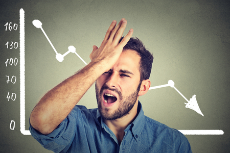 risky job: Portrait frustrated stressed young man desperate with financial market chart graphic going down on grey office wall background. Poor economy financial crisis concept. Face expression, emotion
