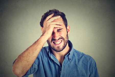 Portrait stressed man suffering from headache isolated on gray wall background