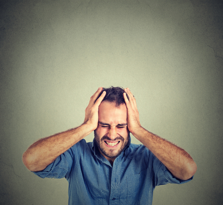 caras: stressed man upset frustrated isolated on gray wall background. Negative human emotions