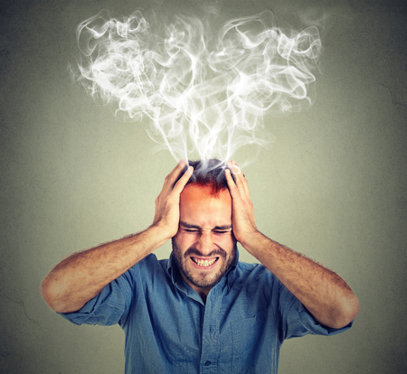 Portrait young stressed man screaming thinking too hard steam coming out up of head isolated on grey wall background. Face expression emotion perception 스톡 콘텐츠