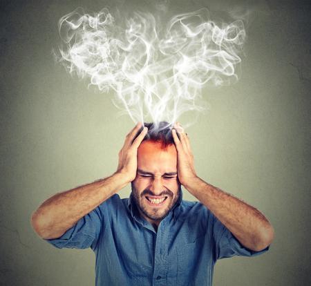 Portret jonge beklemtoonde man schreeuwen denken te hard stoom uit up van het hoofd die op grijze muur achtergrond. Uitdrukking van het gezicht emotie waarneming